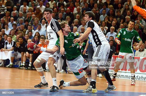 Manuel Spaeth of Goeppingen fights for the ball with Kim Andersson and Christian Sprenger of Kiel during the Handball Bundesliga match between Frisch...