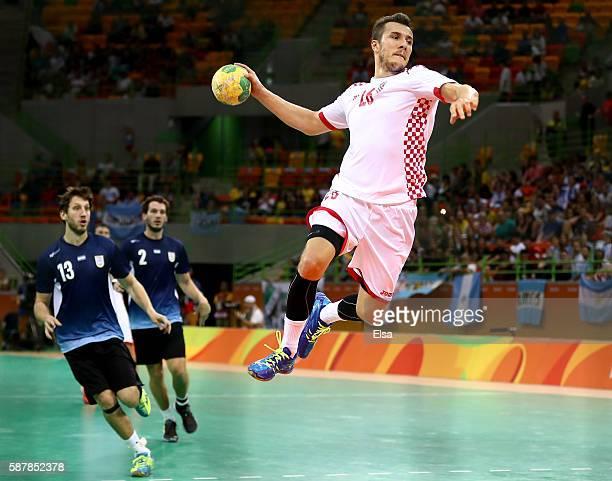 Manuel Strlek of Croatia takes a breakaway shot as Juan Pablo Fernandez and Federico Fernandez of Argentina defend on Day 4 of the Rio 2016 Olympic...
