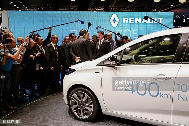 Manuel Valls, France's prime minister, center, stands beside a new battery-powered Zoe city car, manufactured by Renault SA, during the second press...