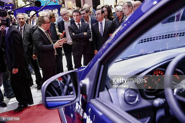 Manuel Valls, France's prime minister, center, visits the Renault exhibition stand with Carlos Ghosn, chief executive officer of Renault SA and...