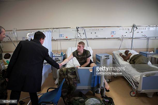 Manuel Valls, Minister of the Interior shakes the hand of a soldier in a hospital during his visit to the region on February 15, 2013 in Afghanistan.
