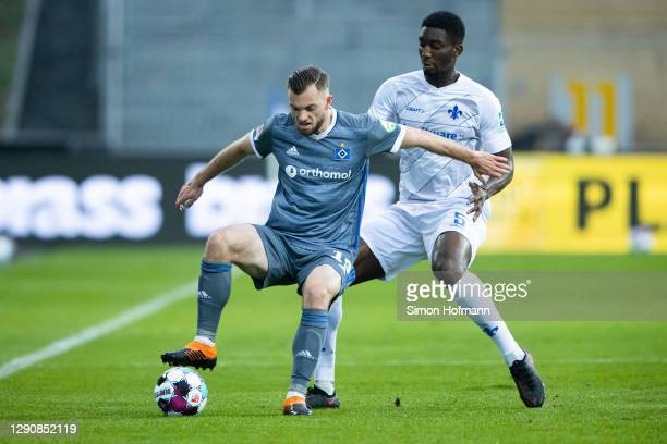 Manuel Wintzheimer of Hamburg is challenged by Patric Pfeiffer of Darmstadt during the Second Bundesliga match between SV Darmstadt 98 and Hamburger...