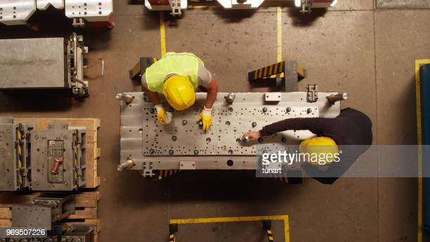 manuel worker in a production line of a machine part - making stock pictures, royalty-free photos & images