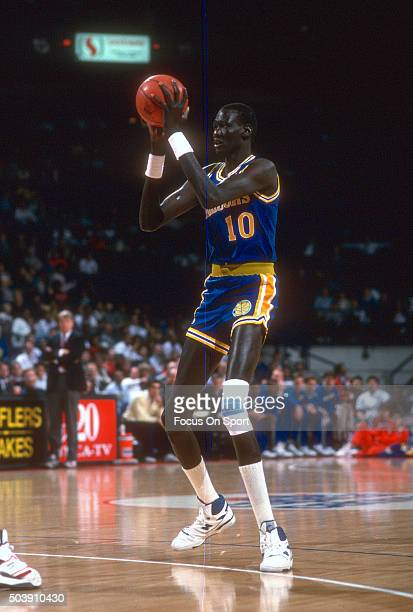 Manule Bol of the Golden State Warriors looks to pass the ball against the Washington Bullets during an NBA basketball game circa 1989 at the Capital...