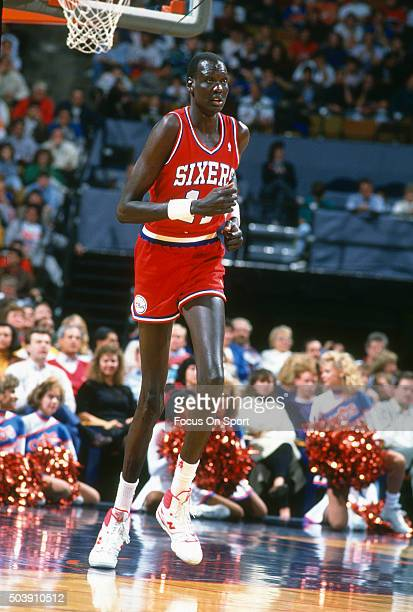 Manule Bol of the Philadelphia 76ers runs up court against the Cleveland Cavaliers during an NBA basketball game circa 1990 at the Coliseum at...