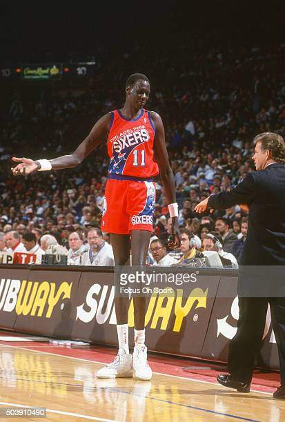 Manule Bol of the Philadelphia 76ers talks with coach Jim Lynam against the Washington Bullets during an NBA basketball game circa 1992 at the...