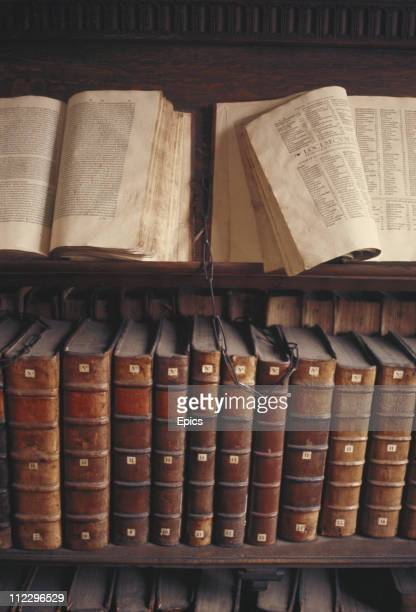 Manuscripts and antique books are kept chained on lecterns and bookshelves in Trinity college library Cambridge University Cambridgeshire circa 1975