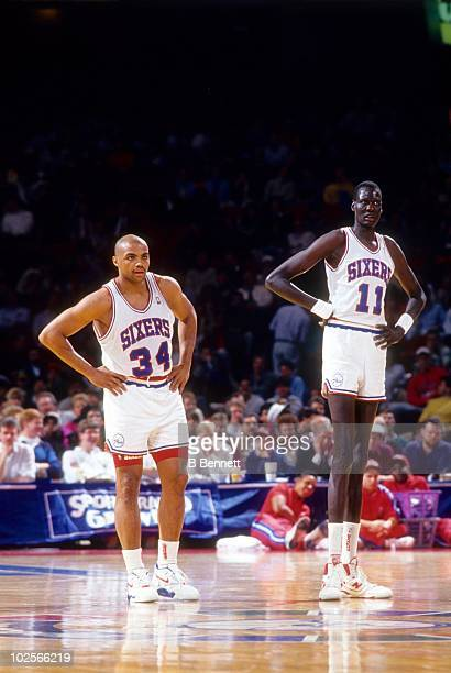 Manute Bol and teammate Charles Barkley of the Philadelphia 76ers stand on the court during an NBA game circa 1991 at the Spectrum in Philadelphia...