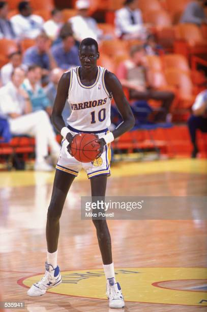 Manute Bol of the Golden Sate Warriors looks to move the ball during a game