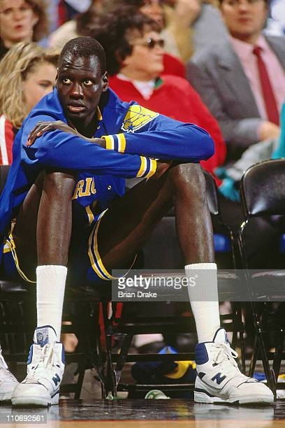 Manute Bol of the Golden State Warriors sits on the bench against the Portland Trailblazers during a game played at Memorial Coliseum in Portland...