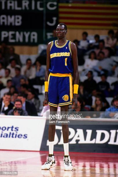 Manute Bol of the Golden State Warriors takes the court during a 1995 NBA game NOTE TO USER User expressly acknowledges that by downloading and or...