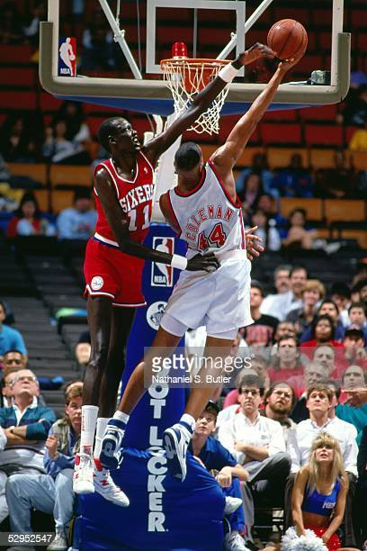 Manute Bol of the Philadelphia 76ers goes up to block a shot by Derrick Coleman of the New Jersey Nets during an NBA game at the Brendan Byrne Arena...
