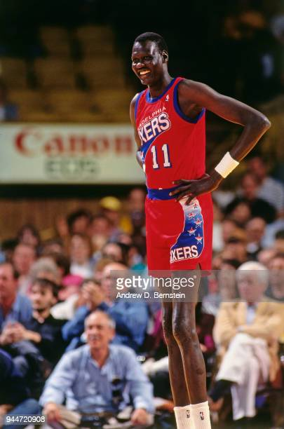 Manute Bol of the Philadelphia 76ers looks on during the game against the Los Angeles Lakers on March 5 1993 at the Great Western Forum in Inglewood...