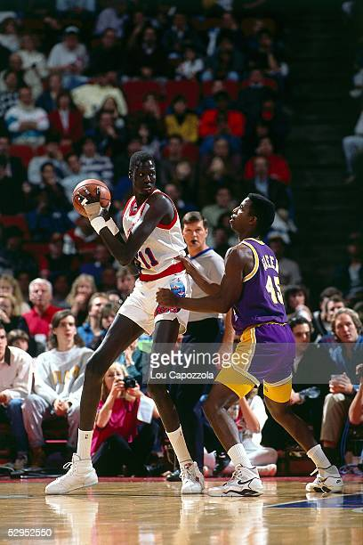 Manute Bol of the Philadelphia 76ers posts up against the Los Angeles Lakers during an NBA game at the Spectrum circa 1991 in Philadelphia...