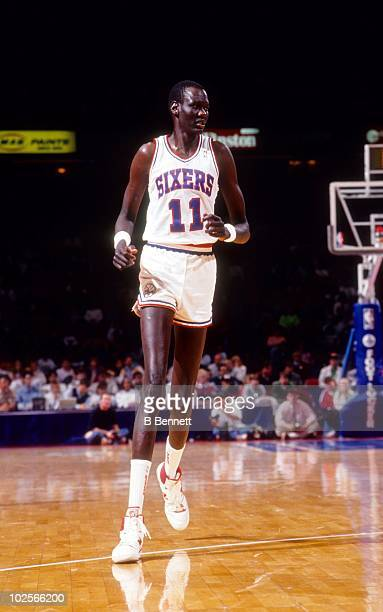 Manute Bol of the Philadelphia 76ers runs up the court during an NBA game circa 1991 at the Spectrum in Philadelphia Pennsylvania