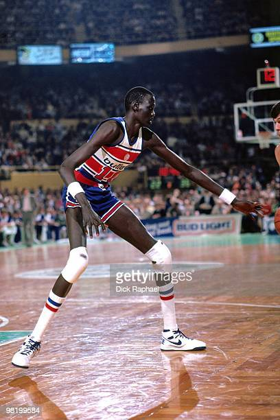 Manute Bol of the Washington Bullets defends against the Boston Celtics during a game played in 1985 at the Boston Garden in Boston Massachusetts...