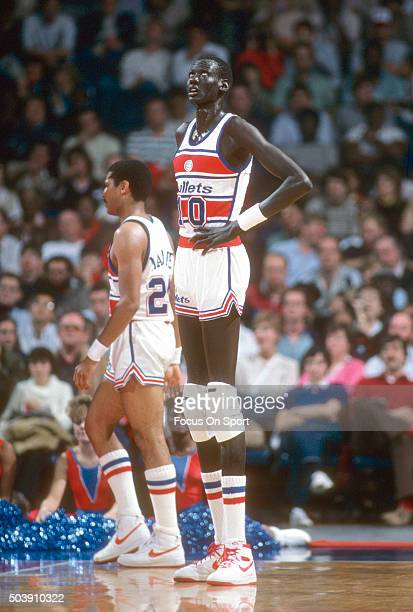Manute Bol of the Washington Bullets looks on during an NBA basketball game circa 1985 at the Capital Centre in Landover Maryland Bol played for the...