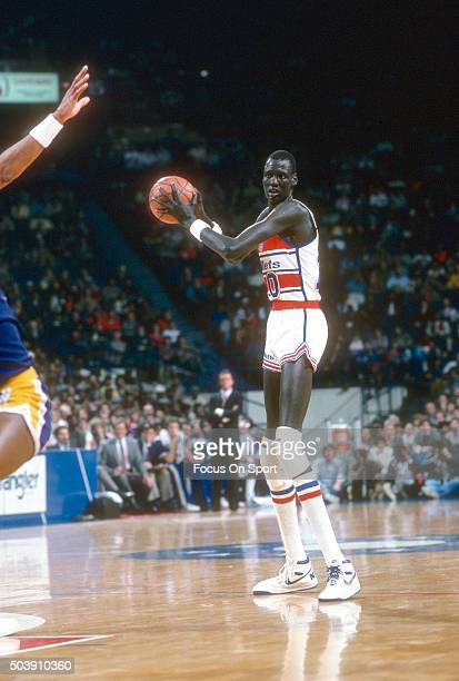 Manute Bol of the Washington Bullets looks to pass the ball against the Los Angeles Lakers during an NBA basketball game circa 1986 at the Capital...