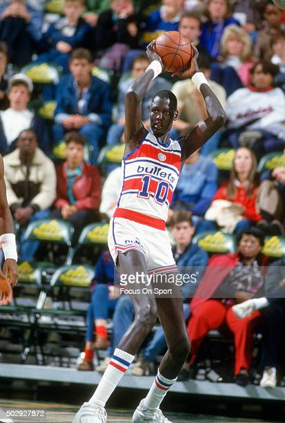 Manute Bol of the Washington Bullets looks to pass the ball during an NBA basketball game circa 1986 at the Capital Centre in Landover Maryland Bol...