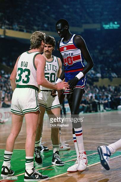 Manute Bol of the Washington Bullets sets a screen on Larry BIrd of the Boston Celtics during a game played in 1987 at the Boston Garden in Boston...