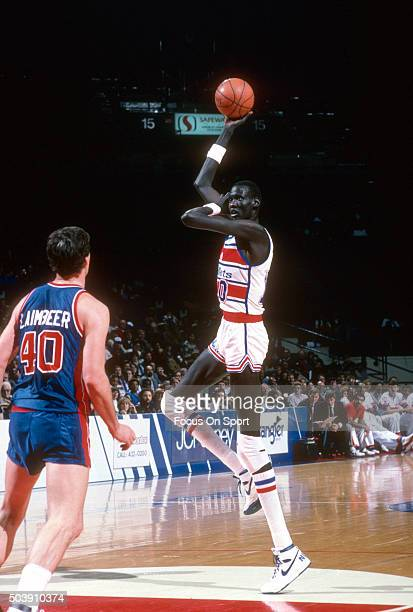Manute Bol of the Washington Bullets shoots against the Detroit Pistons during an NBA basketball game circa 1986 at the Capital Centre in Landover...