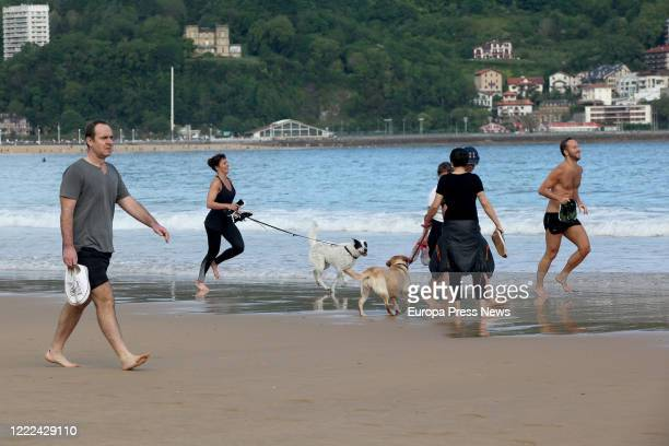 Many adults walk along La Concha beach on the day when the government allows them to go out for individual sports and to walk with another person...