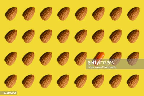 many almonds arranged on yellow background and one capsule - almond stock pictures, royalty-free photos & images