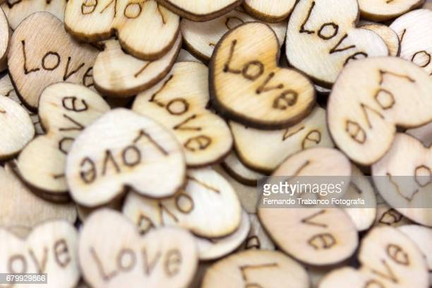 Many and repeated wooden hearts with the word love. Gift on Valentine's Day.