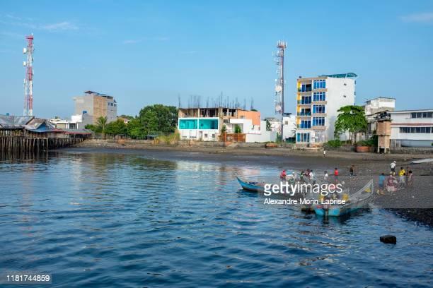many black men embarking with goods on small speed boats in the port - only men stockfoto's en -beelden