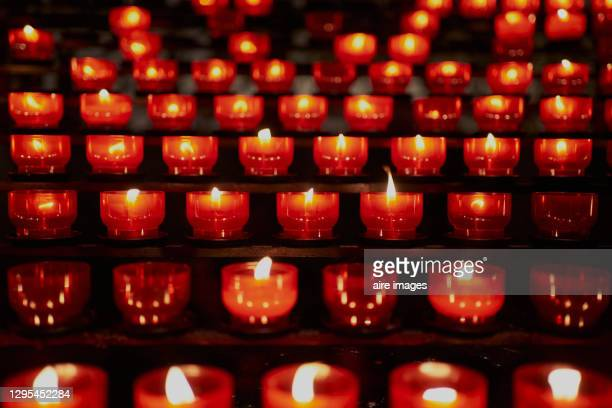 many candles lit in dark church - candle stock pictures, royalty-free photos & images