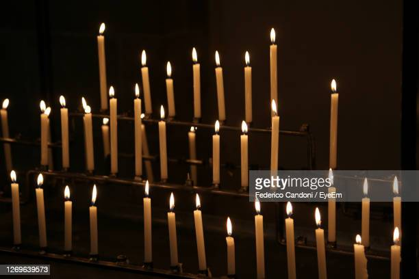 many candles made with wax with flames during religion mass in the church - vatican stock pictures, royalty-free photos & images