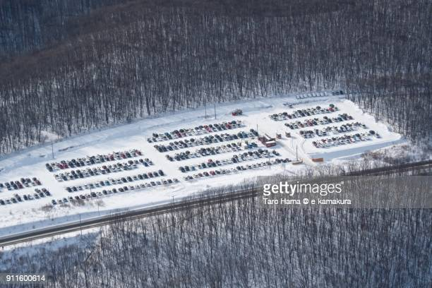 Many cars parking snow covered parking lots near New Chitose Airport in Hokkaido in Japan in winter daytime aerial view from airplane