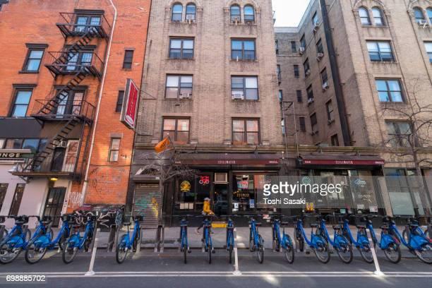 many citi bikes in the dock at east village street manhattan new york city. - east village stock-fotos und bilder