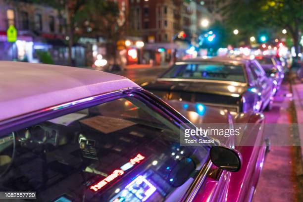 many classic cars stop on the second avenue at east village in the midnight for some movie or tv shooting at new york ny usa on aug. 10 2018. - east village stock pictures, royalty-free photos & images