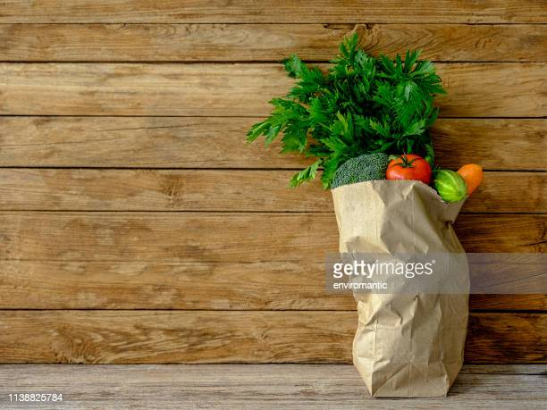 beaucoup de légumes colorés de salade de couleur de contraste dans un sac de magasinage de supermarché de papier brun sur une vieille table en bois contre un vieux mur de fond patiné de panneau de bois. - bag photos et images de collection