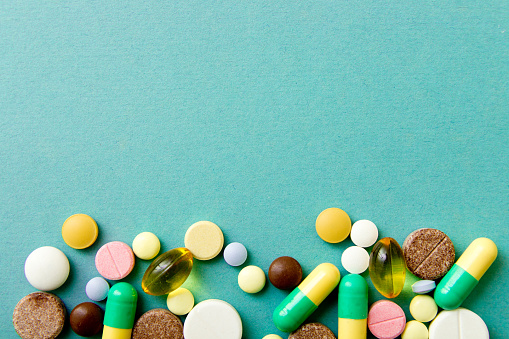 Many colorful pills on red background with copy space. Pattern , Identification of pills 914792268