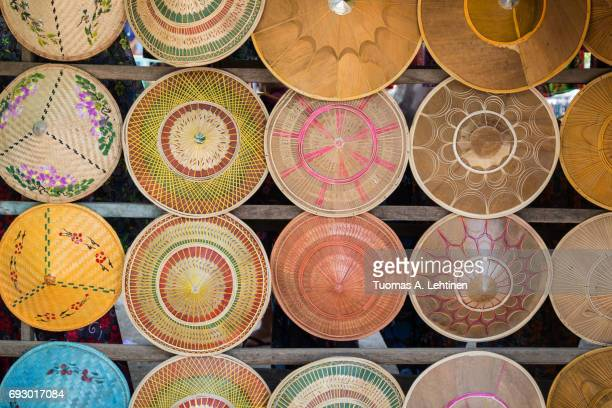 many colorful woven asian conical hats (also known as asian rice hats or farmer's hats) for sale in myanmar (burma). - chapeau chinois photos et images de collection