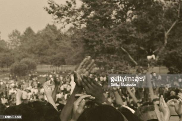 Many colors of humanity with hands clapping over their heads, man in tree at the 1st Elysian Park Love-In on March 26, 1967 in Los Angeles,...