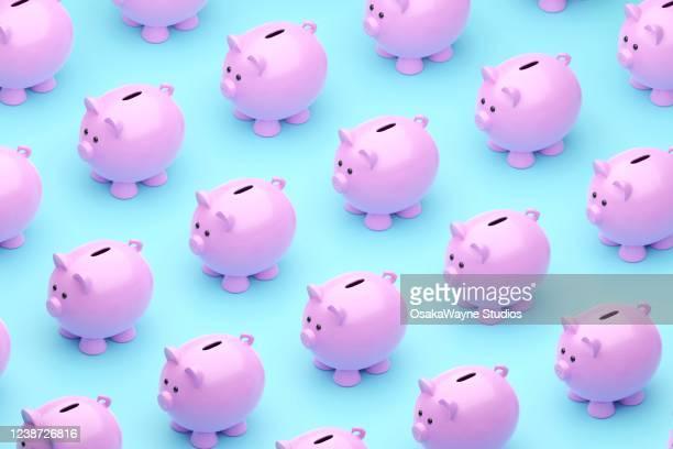 many cute piggy banks on blue background - geld stockfoto's en -beelden