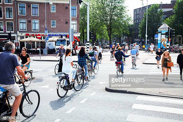 Many cycling people crossing Prins Henrikkadde in Amsterdam
