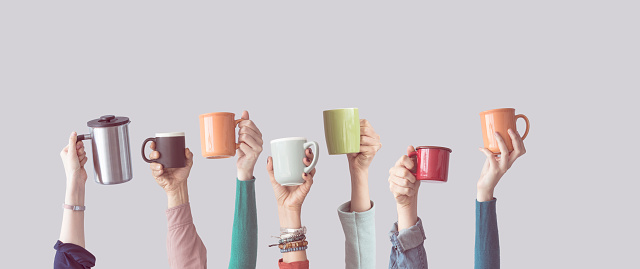 Many different arms raised up holding coffee cup 928328352