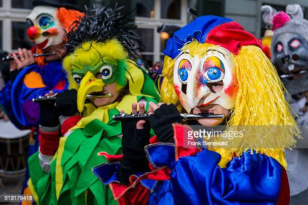 Many different groups of masked people walk through the streets of Basel for 3 days and nights at Basler Fasnacht playing music all the time