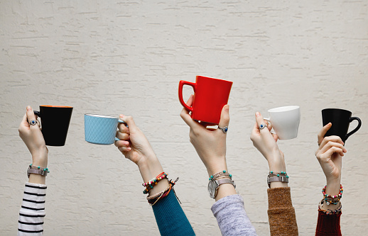 Many different hands holding coffee cups. 1086988552