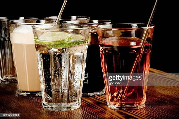 Many drinks in a glass on a wooden countertop