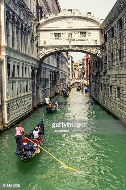 Many gondolas navigating under the Bridge of Sighs in Venice