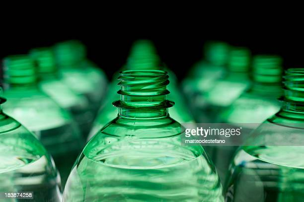 Many green bottles organized in lines
