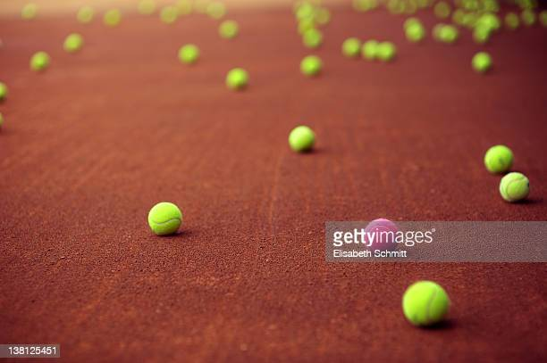 Many green tennis-balls plus one pink tennis-ball