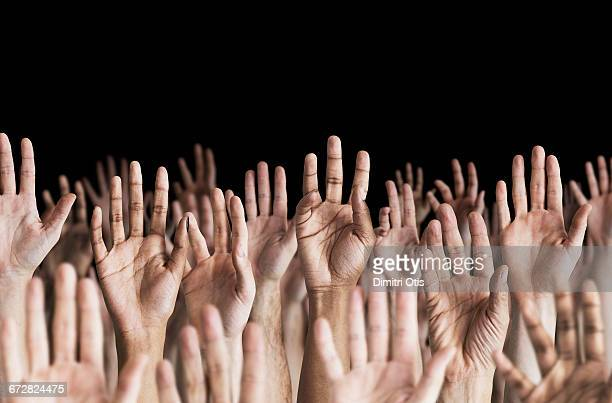 Many hands in the air, black background