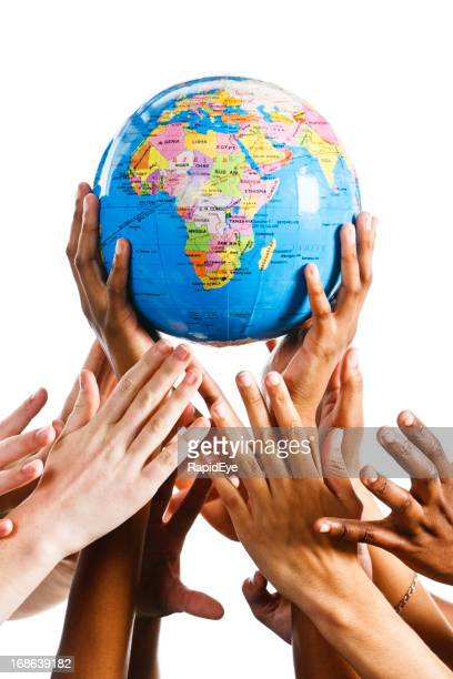 Many hands reach for a globe of the earth