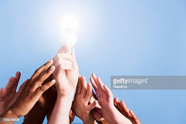 Viele Hände bis zu helles Licht, das durch ein